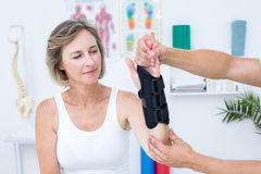 Doctor examining his patients wrist Royalty Free Stock Photos