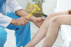 Doctor examining the knee reflex stock images
