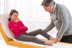 Doctor a Examining la rodilla herida de una muchacha adolescente foto de archivo