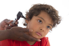 Doctor examining little boy's ears. Hysician performing ear examination during a visit Royalty Free Stock Images
