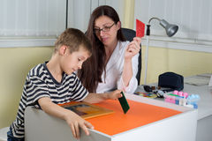 Doctor Examining Little Boy's Logical Thinking With Colored Geometric Shapes in Consulting Room Stock Photo