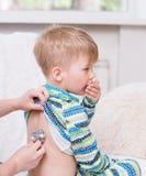 Doctor examining little boy with stethoscope stock photo