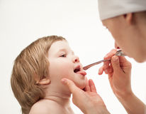 Doctor examining little girl's throat Stock Photography