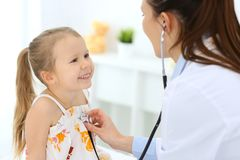 Doctor examining a little girl by stethoscope. Happy smiling child patient at usual medical inspection. Medicine and. Healthcare concepts stock images
