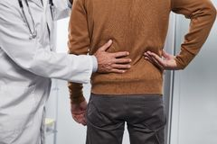 Doctor examining lumbar spine of his patient stock photography