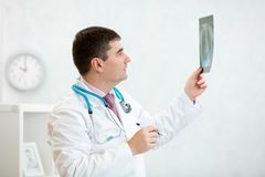 Doctor examining a lung radiography. Male doctor examining a lung radiography in office royalty free stock image