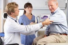 Doctor Examining Male Patient With Elbow Pain. With Nurse Royalty Free Stock Images