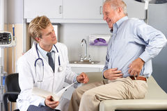 Doctor Examining Male Patient With Hip Pain. In Hospital Stock Image
