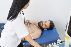 Doctor Examining Male Patient With Ultrasound Machine stock photography