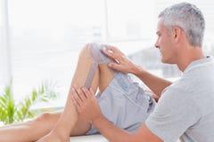 Doctor examining man leg Royalty Free Stock Image