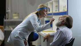 Doctor examining man`s throat with tongue depressor stock footage