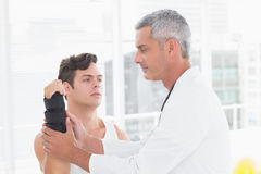 Doctor examining a man wrist. Doctor examining a men wrist in medical office stock images