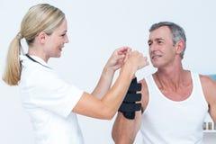 Doctor examining a man wrist Stock Photo