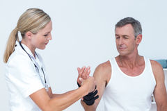 Doctor examining a man wrist Stock Image