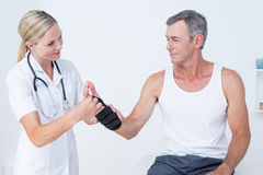 Doctor examining a man wrist Stock Images