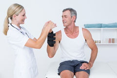 Doctor examining a man wrist Royalty Free Stock Image