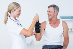 Doctor examining a man wrist. Doctor examining a men wrist in medical office Royalty Free Stock Photos