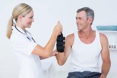 Doctor examining a man wrist Royalty Free Stock Photos