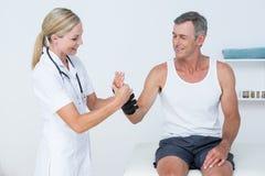 Doctor examining a man wrist Stock Photography
