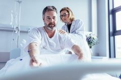 Doctor examining mature man in hospital bed Stock Photography