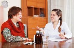 Doctor examining mature woman at table Royalty Free Stock Image