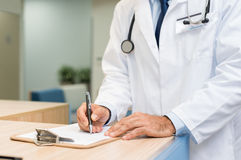 Doctor examining medical report. Close up hands of doctor writing on a document on clipboard. Senior surgeon checking form and making changes at reception desk Stock Image