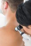 Doctor examining melanoma on back of man Royalty Free Stock Photos