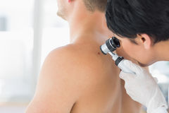 Doctor examining mole on back of man Stock Photos