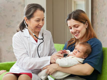 Doctor examining newborn baby Stock Photos