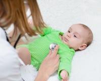 Doctor examining newborn baby with stethoscope Stock Photos