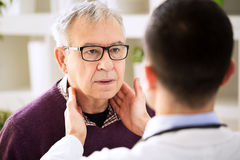 Doctor examining old patient lymph glands. Throat inflammation Stock Images