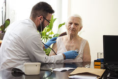Doctor examining an old woman with a stethoscope in a doctor`s office. Doctor examining an old women with a stethoscope in a doctor`s office Royalty Free Stock Photos