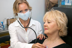 Doctor, examining patient. Young female doctor, examining patient royalty free stock photo