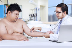 Doctor examining patient heartbeat Royalty Free Stock Photo