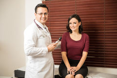 Doctor examining patient in his office. Portrait of a handsome Hispanic doctor standing next to a female patient and smiling Royalty Free Stock Photography