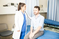 Doctor examining patient in hospital. Beautiful young latin female doctor checking male patient with stethoscope in hospital room Stock Photos
