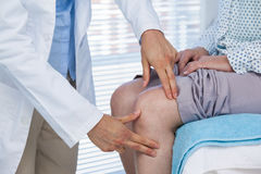 Doctor examining patient knee. Mid section of doctor examining patient knee in clinic Royalty Free Stock Photo