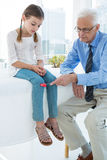 Doctor examining patient knee by using test hammer Royalty Free Stock Photography
