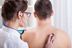 Doctor examining patient lungs. Young doctor examining patient lungs by stethoscope royalty free stock photos