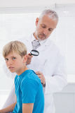 Doctor examining patient with magnifying glass Stock Photography