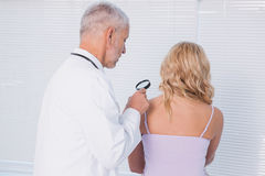 Doctor examining patient with magnifying glass Royalty Free Stock Photo