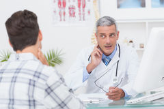 Doctor examining patient with neck ache Stock Photos