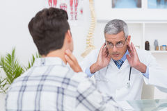 Doctor examining patient with neck ache Stock Image