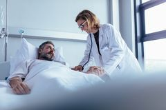 Doctor examining patient pulse in hospital room. Hospitalized men lying in bed while doctor checking his pulse. Female physician examining male patient in stock photos