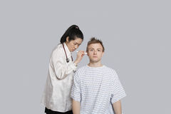Doctor examining patient's ear with flashlight Royalty Free Stock Photo