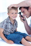 Doctor examining a patient' s ears. With a otoscope Stock Photos