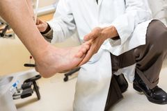 Doctor Examining Patient's Foot In Hospital Stock Image