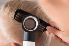 Doctor Examining Patient's Hair Through Dermatoscope Stock Photos
