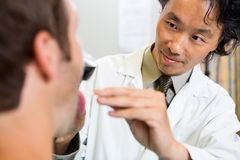 Doctor Examining Patient's Mouth In Hospital Stock Photo