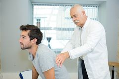 Doctor examining patient shoulder in medical office royalty free stock photo